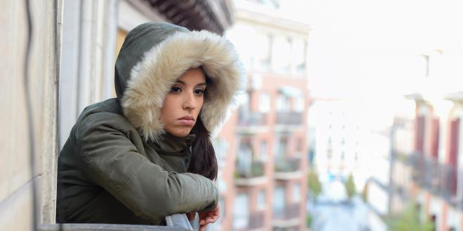 a depressed woman looking out at the city